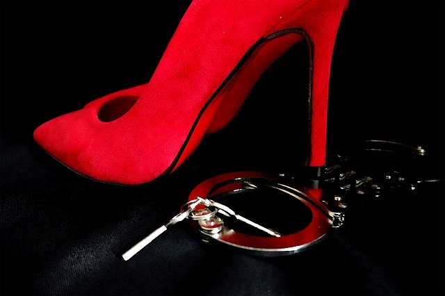 a red high-heel stepping on cuffings