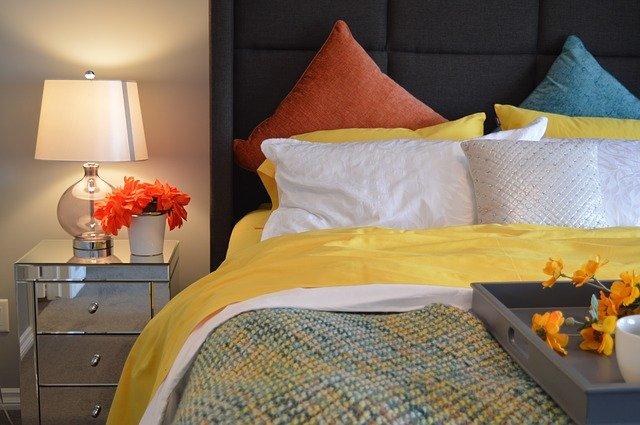 postel s barevnými polštáři a lampa na nočním stolku