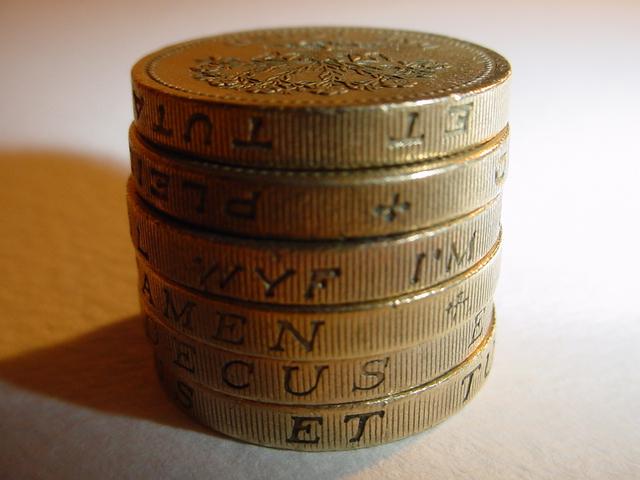 kovové mince složené na sobě se stínem na stůl
