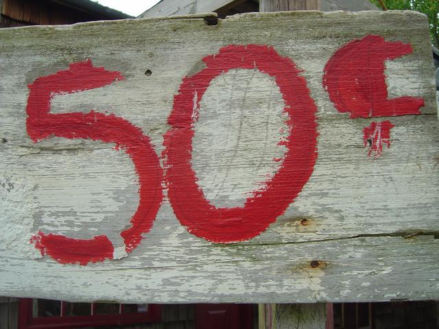 cena napsaná červenou barvou na staré dřevo