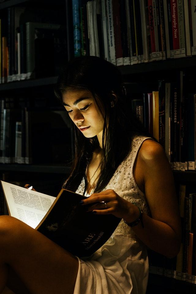 žena v osvětleném prostoru čte knihu